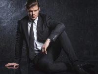 attractive young fashion model in black suit and tie is resting on studio floor